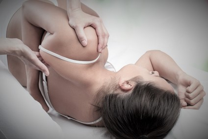 Physiotherapist doing healing treatment on female shoulder blade.